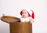baby wearing Christmas Santa hat in wicker basket