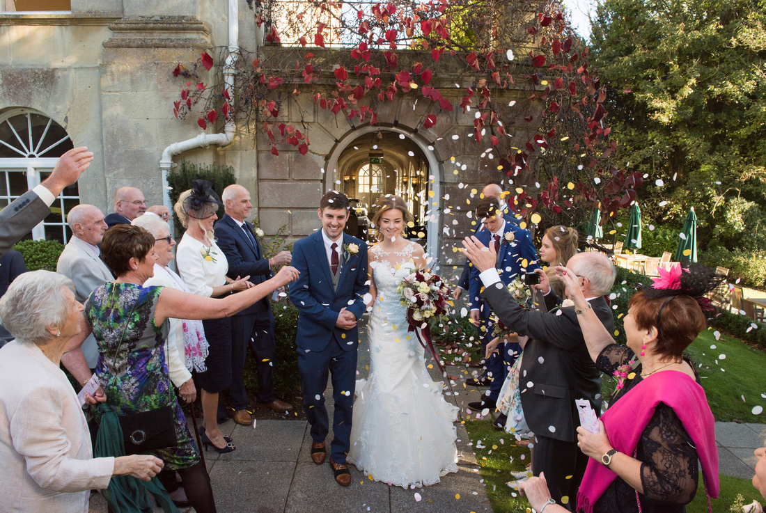 Bride and groom at their wedding being shoewred with confetti at Bailbrook House Hotel, Bath, Somerset. Beata Cosgrove Photography
