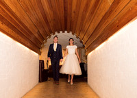 bride and groom walking together down arched corridor