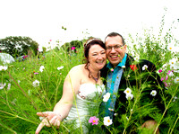 Bride and groom among wild flowers in garden