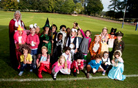 Group of children in costumes with their teacher outdoors posing on a rugby pitch