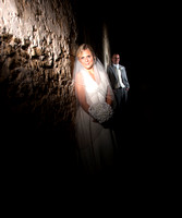 Bride illuminated by ray of light; groom in background
