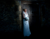 Bride in white dress holding flowers in barn